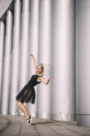 Photo pour Belle fille en jupe noire danse près de colonnes - image libre de droit