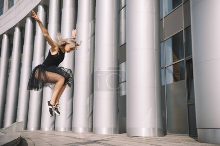low angle view of beautiful young ballerina jumping and dancing on street