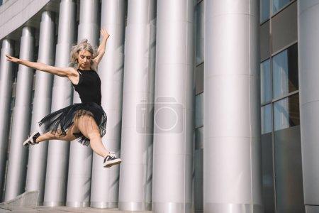 Photo pour Vue faible angle de jeune ballerine sautant et dansant dans la rue - image libre de droit
