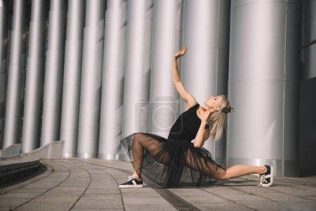 attractive young ballerina in black skirt dancing on street