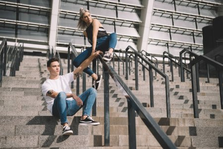 Stylish sporty young couple with backpacks sitting...