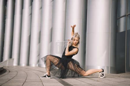 beautiful young ballerina in black skirt dancing on street