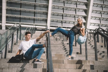Photo for Stylish sporty young couple with backpacks posing on stairs - Royalty Free Image