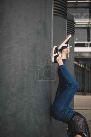 low section of girl standing upside down near columns
