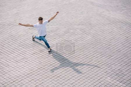 high angle view of handsome young man performing contemporary dance on street