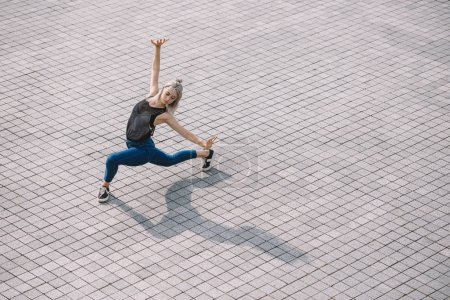 high angle view of beautiful girl performing contemporary dance on street