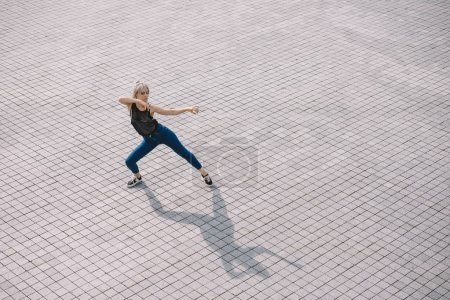 high angle view of young woman performing contemporary dance on street