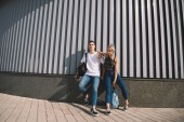 beautiful stylish young couple with backpacks standing in city