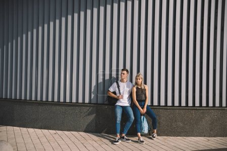 Photo for Beautiful young couple with backpacks standing together on street - Royalty Free Image