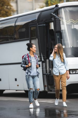 Photo for Selective focus of multicultural women with backpacks walking near travel bus at urban street - Royalty Free Image