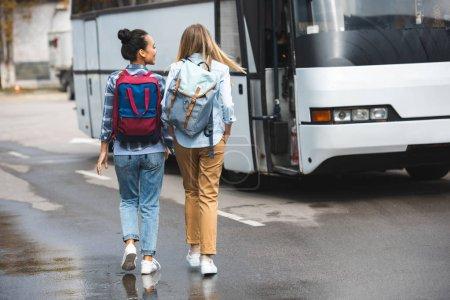 Photo pour Vue arrière des femmes avec des sacs à dos marchant près du bus de voyage dans la rue urbaine - image libre de droit