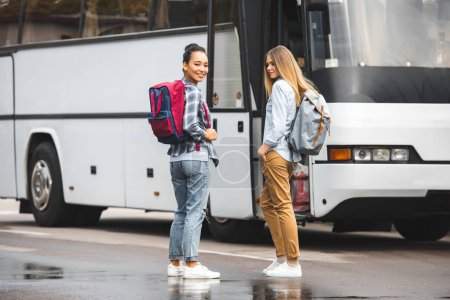 young multiethnic women with backpacks posing near travel bus at urban street