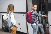 """Постер, картина, фотообои """"молодой многонациональное женщин путешественников с рюкзаками, ходить в путешествия автобус на улице"""""""