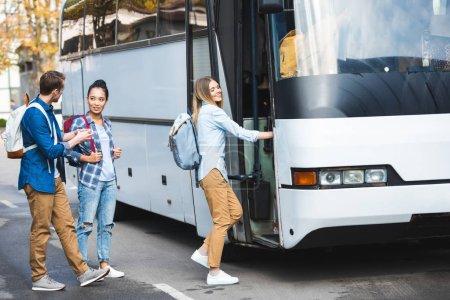 Photo pour Mise au point sélective de multiethniques touristes avec sacs à dos de randonnée pédestre dans les bus de voyage à la rue de la ville - image libre de droit