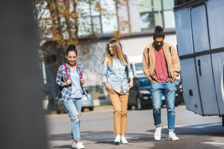 selective focus of young multiethnic friends with rucksacks walking near bus at city street