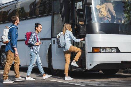 Photo pour Vue de côté d'amis multiculturelles avec sacs à dos, marche en bus de voyage à rue - image libre de droit