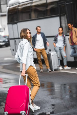 Photo for Beautiful female tourist carrying wheeled bag while her friends waiting near travel bus at city street - Royalty Free Image