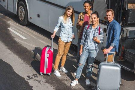 Foto de Vista de ángulo alto de amigos multiétnicas con ruedas bolsos posando cerca autobús del recorrido en la calle de la ciudad - Imagen libre de derechos