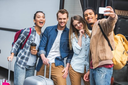 happy mixed race man taking selfie with multicultural friends on smartphone near travel bus at street