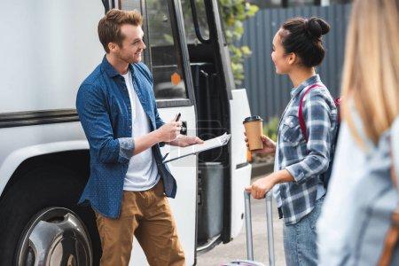 Foto de Controlador de macho bus sonriente en Portapapeles mientras mujer asiática con taza de café cerca de autobús en la calle urbanita - Imagen libre de derechos