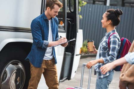 Foto de Controlador de bus hombre feliz escribiendo en Portapapeles mientras mujer asiática con taza de café desechables cerca de autobús en la calle - Imagen libre de derechos