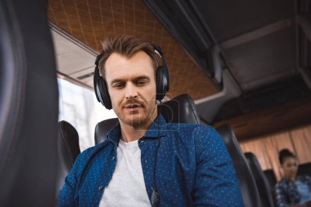 adult man in headphones listening music and looking down during trip on travel bus