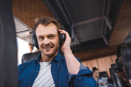 Photo pour Portrait de l'homme au casque écoute musique et regardant la caméra pendant voyage bus voyage - image libre de droit