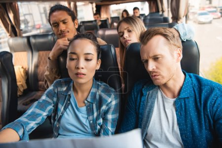 Photo for Pensive multiethnic tourists looking at map during trip on travel bus - Royalty Free Image