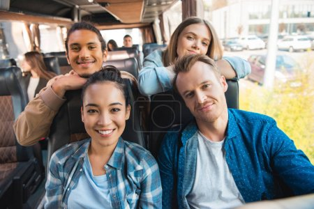 portrait of happy multicultural friends looking at camera during trip on travel bus