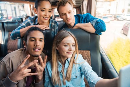 Foto de Felizes amigos multiétnicos tomar selfie en smartphone durante el viaje autobús de viaje - Imagen libre de derechos