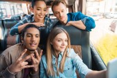 happy multiethnic friends taking selfie on smartphone during trip on travel bus