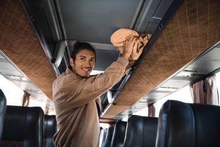 smiling young multiracial man putting rucksack on shelf in travel bus