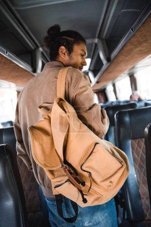 Foto de Vista trasera del turista macho raza mixta con mochila en el autobús del recorrido - Imagen libre de derechos
