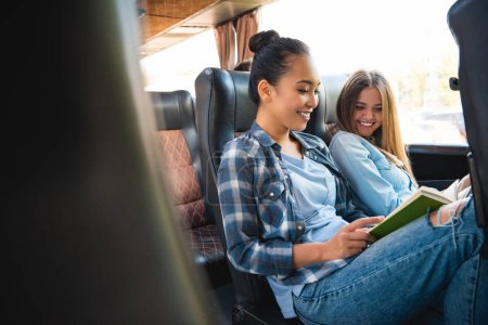 laughing multiethnic female friends reading book during trip on travel bus
