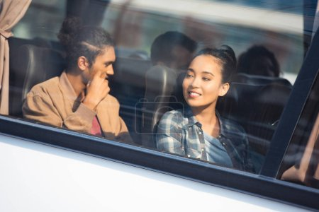 young interracial couple of tourists during trip on travel bus