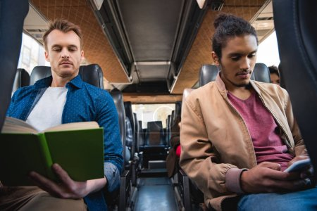 multiracial young man using smartphone while his male friend reading book during trip on bus