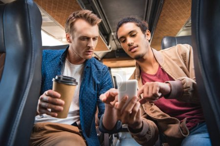 young mixed race man showing smartphone to his male friend with paper coffee cup during trip on bus