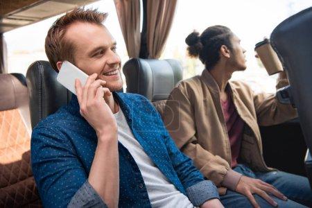 Photo pour Homme souriant parle sur smartphone tandis que son ami de boire du café près de hautes sur bus de voyage - image libre de droit