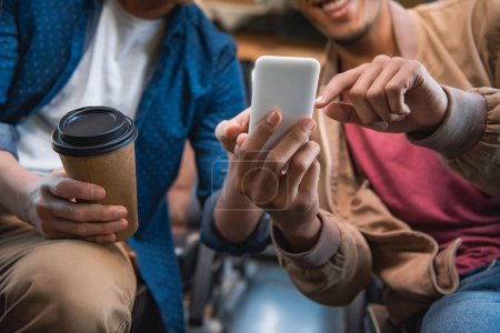 cropped image of man pointing at smartphone to his male friend with disposable cup of coffee during trip on travel bus