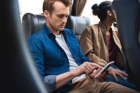 Photo for Adult man using smartphone while his friend sitting near in travel bus - Royalty Free Image