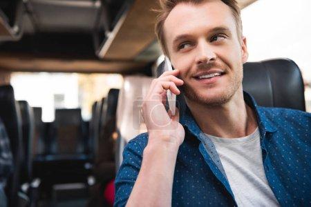 Photo pour Heureux voyageur mâle parler sur smartphone lors de voyage sur bus - image libre de droit