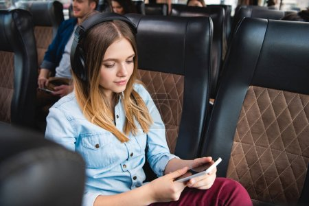 Photo pour Jeune femme en casque écoute la musique et à l'aide de smartphone pendant voyage bus voyage - image libre de droit