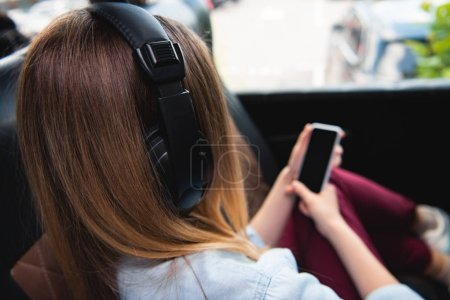 rear view of female traveler in headphones listening music and using smartphone during trip on bus