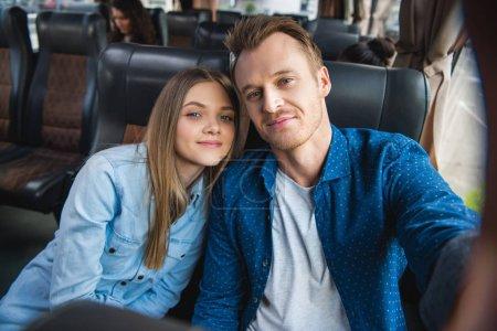 Photo pour Adulte homme heureux prenant selfie avec superbe copine pendant voyage bus voyage - image libre de droit