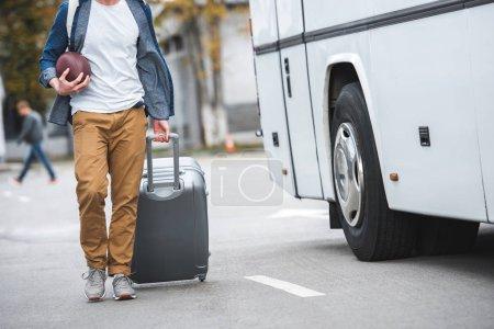 Photo pour Vue partielle de l'homme avec le ballon de rugby sacoche sur roues près de voyage bus à rue - image libre de droit