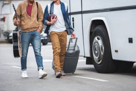 Foto de Vista parcial del hombre con pelota de rugby lleva ruedas bolsa mientras su amigo caminando cerca autobús del recorrido en la calle - Imagen libre de derechos