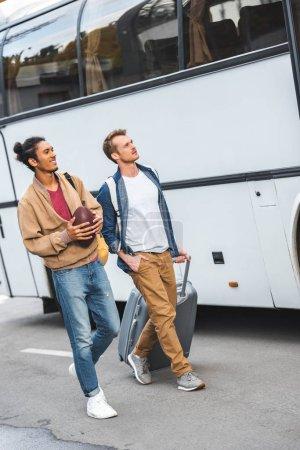 Photo pour Multiracial jeune homme marchant avec ami sacoche sur roues près de bus à la rue de la ville de ballon de rugby - image libre de droit