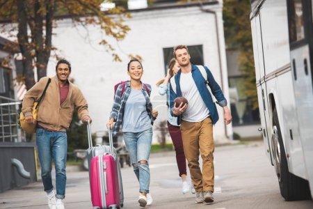 Foto de Amigos alegres joven con bolsas de ruedas y pelota de rugby corriendo cerca de autobús en la calle de la ciudad de viajes - Imagen libre de derechos