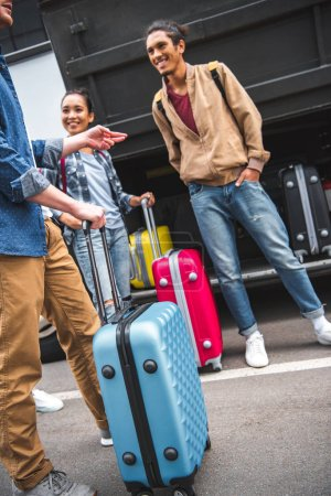 Foto de Imagen recortada del hombre con el bolso con ruedas gesticulando y hablando con amigos multiculturales cerca de autobús en la calle - Imagen libre de derechos