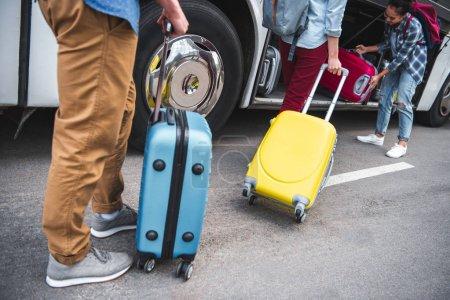 sac à roues mise de femme en bus de voyage alors que ses amis marche près rue urbain